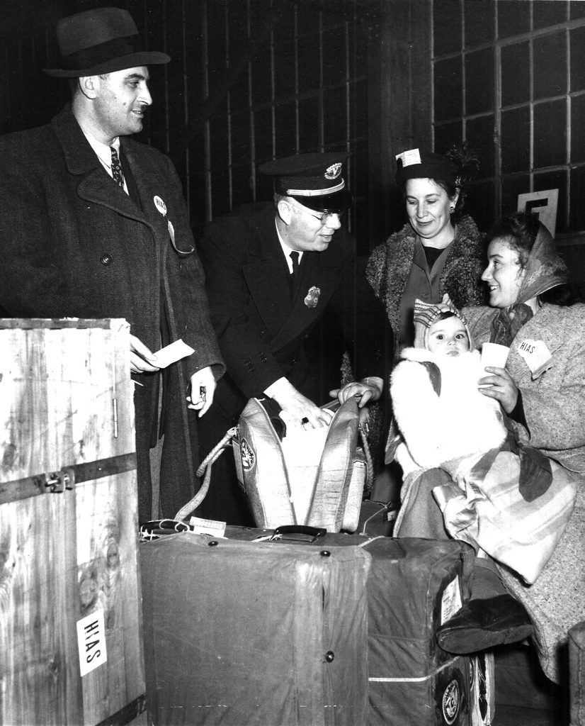 Hebrew Immigrant Aid Society worker welcomes DPs from Eastern Europe at the East Boston Immigration Station, 1948-49. Photograph by permission of the American Jewish Historical Society-New England Archives, Boston, MA.